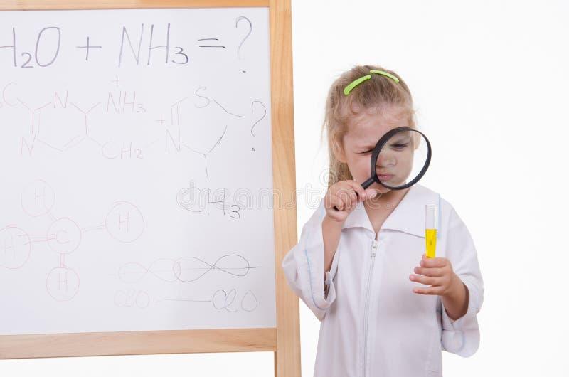 Ο φαρμακοποιός εξετάζει πολύ το υγρό σε έναν σωλήνα δοκιμής στοκ εικόνα με δικαίωμα ελεύθερης χρήσης