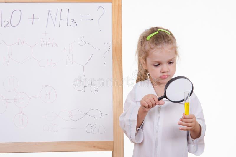 Ο φαρμακοποιός εξετάζει το ρευστό, που στέκεται στον πίνακα στοκ φωτογραφία