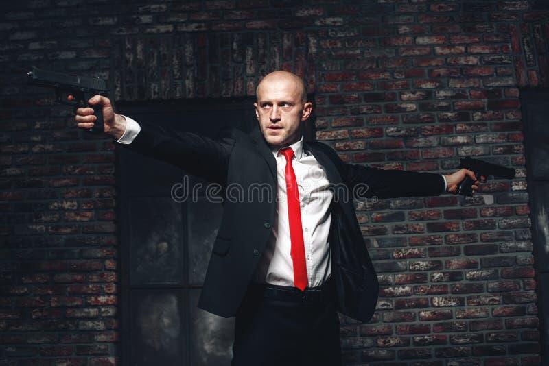 Ο φαλακρός μισθωμένος δολοφόνος στον κόκκινο δεσμό στοχεύει τα πιστόλια στοκ φωτογραφία με δικαίωμα ελεύθερης χρήσης
