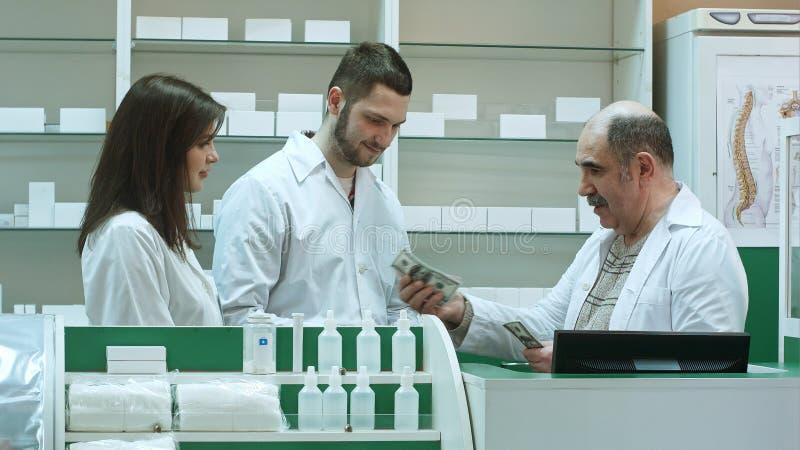 Ο φιλικός ανώτερος φαρμακοποιός δίνει το salalry δολάριο στους συναδέλφους yunger του στοκ φωτογραφία