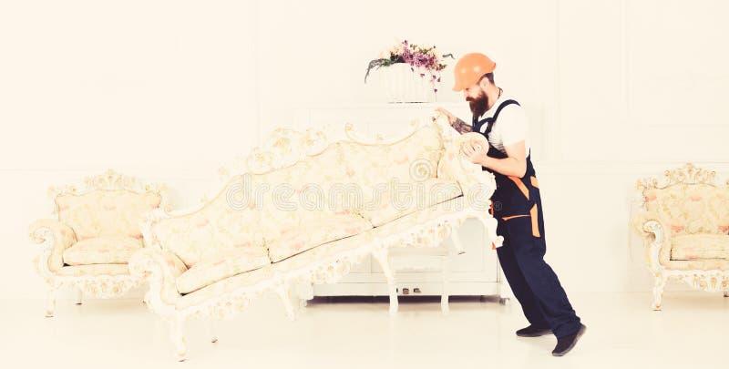Ο φορτωτής κινεί τον καναπέ, καναπές Ο αγγελιαφόρος παραδίδει τα έπιπλα σε περίπτωση κίνησης έξω, επανεντοπισμός E Άτομο με στοκ φωτογραφία