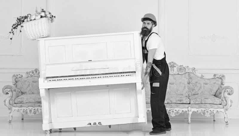 Ο φορτωτής κινεί το όργανο πιάνων Άτομο με τον εργαζόμενο γενειάδων στους ανελκυστήρες κρανών και φορμών επάνω, προσπάθειες να κι στοκ φωτογραφία
