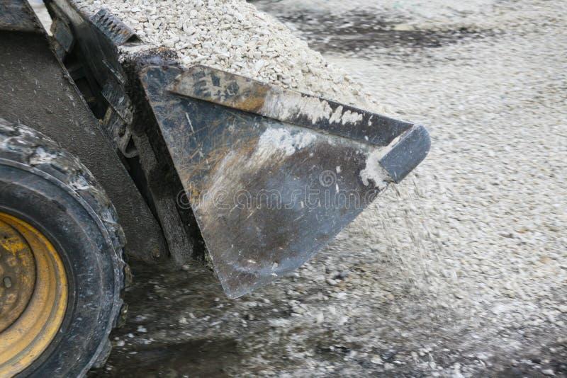 Ο φορτωτής χύνει έξω τη συντριμμένη πέτρα από την κουτάλα στοκ φωτογραφία