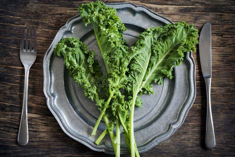 Ο φρέσκος πράσινος Kale στο πιάτο κατανάλωση έννοιας υγιής στοκ εικόνες