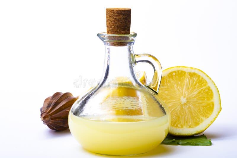 Ο φρέσκος χυμός λεμονιών έκανε από τα ώριμα κίτρινα σισιλιάνα λεμόνια που χρησιμοποιήθηκαν για το μαγείρεμα στο μπουκάλι γυαλιού  στοκ φωτογραφία