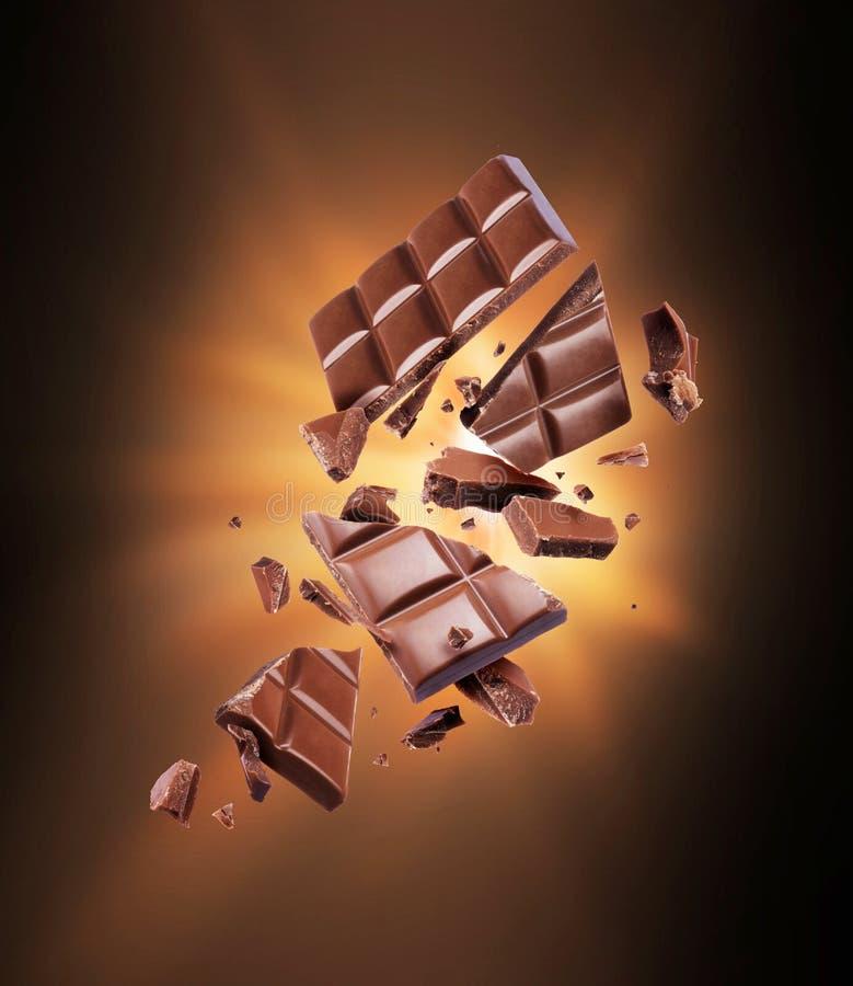 Ο φραγμός σοκολάτας είναι σχισμένος στα κομμάτια στο σκοτάδι στοκ φωτογραφία με δικαίωμα ελεύθερης χρήσης