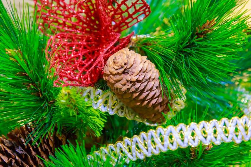 Ο φυσικός κώνος διακοσμεί ένα τεχνητό χριστουγεννιάτικο δέντρο στενό στοκ εικόνα με δικαίωμα ελεύθερης χρήσης