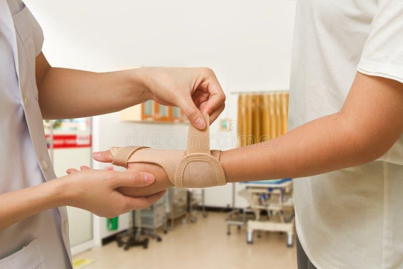 Ο φυσιοθεραπευτής βοηθά τον ασθενή της γυναίκας που φορά ένα στήριγμα καρπών στοκ φωτογραφίες με δικαίωμα ελεύθερης χρήσης