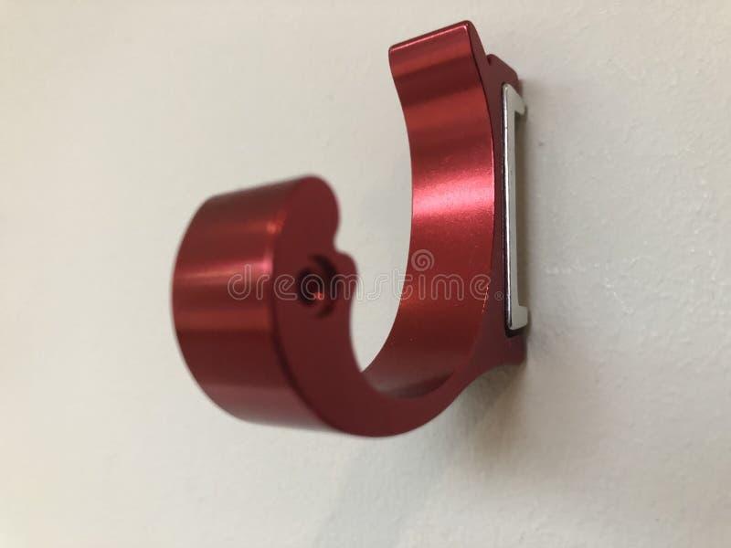 Ο φωτεινός απομονωμένος κόκκινο τοίχος αργιλίου τοποθετεί τους κρεμώντας γάντζους για τις τσάντες ιματισμού στοκ φωτογραφία με δικαίωμα ελεύθερης χρήσης