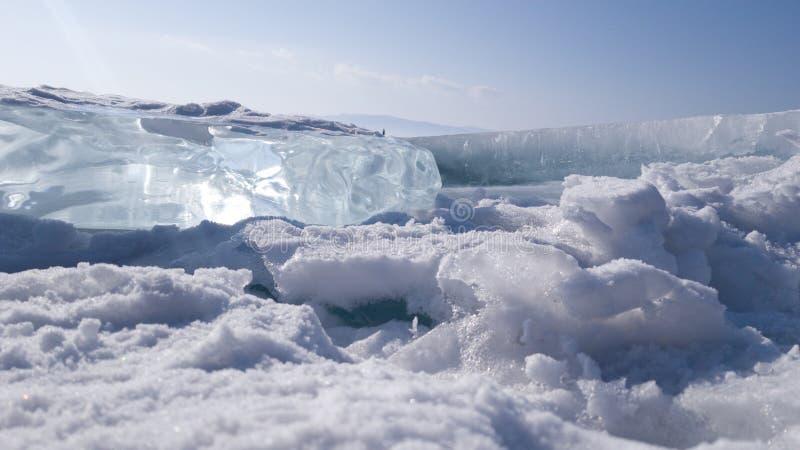 Ο φωτεινός διαφανής μπλε επιπλέων πάγος πάγου βρίσκεται στο χιόνι στην επιφάνεια της λίμνης Baikal Χειμώνας στη Σιβηρία, Ρωσία στοκ εικόνες με δικαίωμα ελεύθερης χρήσης