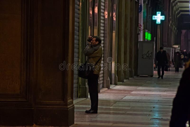 Ο φωτογράφος παίρνει έναν πυροβολισμό κάτω από τα arcades στο στο κέντρο της πόλης Μιλάνο στοκ φωτογραφία
