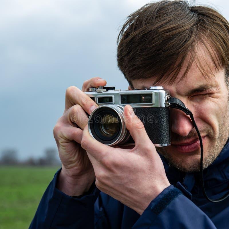 Ο φωτογράφος παίρνει μια εικόνα με μια κάμερα ταινιών σε έναν υπαίθριο στοκ εικόνες