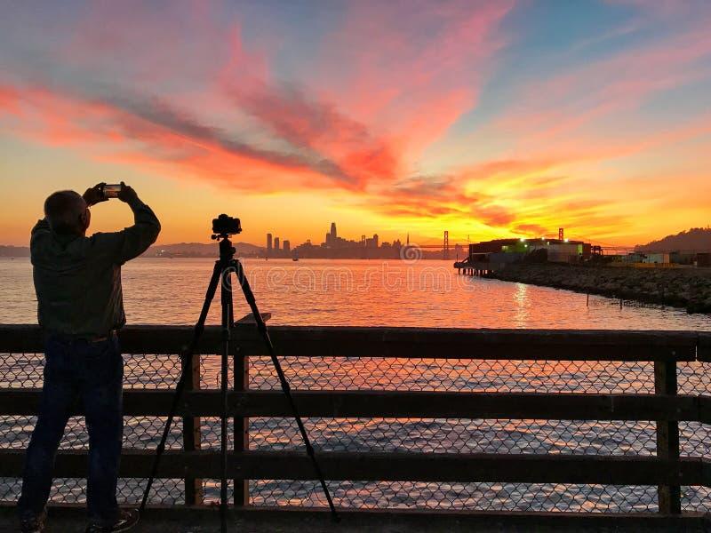 Ο φωτογράφος παίρνει μια εικόνα του ηλιοβασιλέματος με το Σαν Φρανσίσκο στοκ εικόνες με δικαίωμα ελεύθερης χρήσης