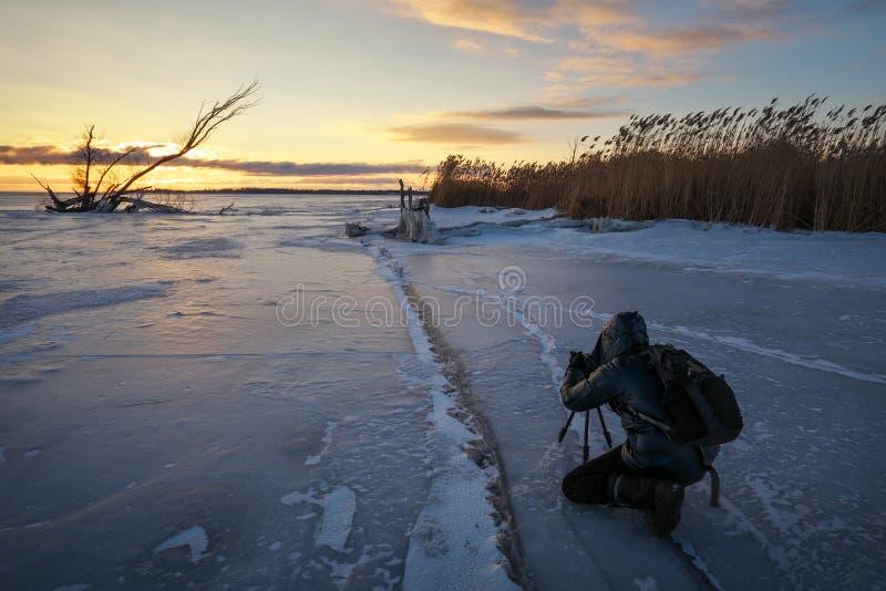 Ο φωτογράφος παίρνει τις εικόνες στον πάγο κοντά στην ακτή στο ηλιοβασίλεμα στοκ φωτογραφία