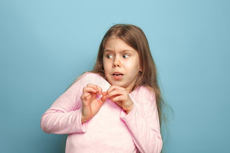 Ο φόβος Κορίτσι εφήβων σε ένα μπλε υπόβαθρο Έννοια εκφράσεων του προσώπου και συγκινήσεων ανθρώπων στοκ φωτογραφίες