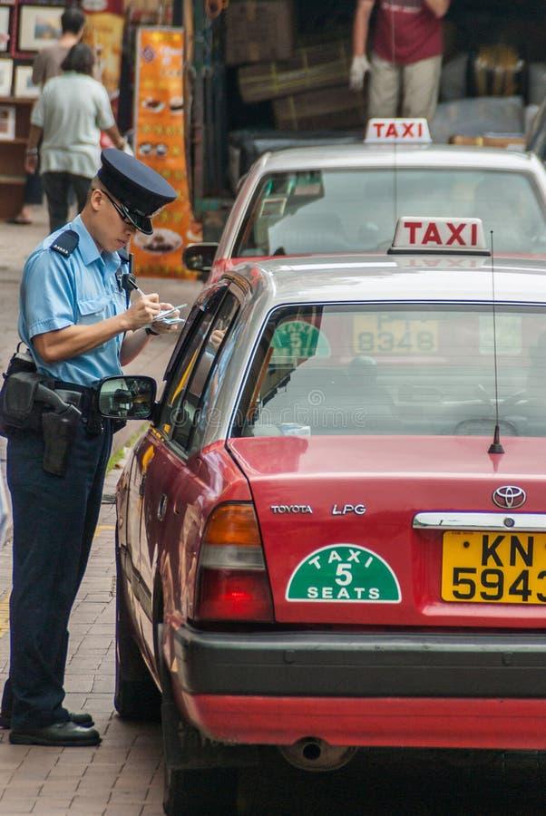 Ο φύλακας κυκλοφορίας γράφει ένα αυτοκίνητο επάνω για την παραβίαση στο νησί Κίνα Χονγκ Κονγκ στοκ εικόνες