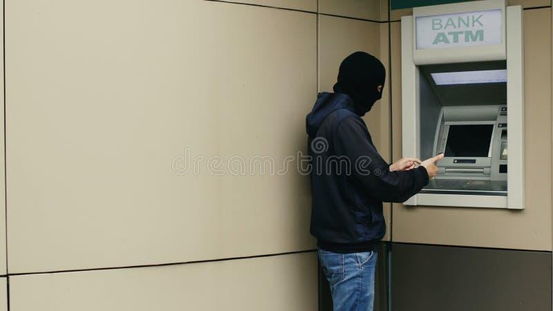 Ο χάκερ ή ο κλέφτης με το smartphone κλέβει τις πληροφορίες ή τα στοιχεία από την τράπεζα ATM στοκ εικόνα