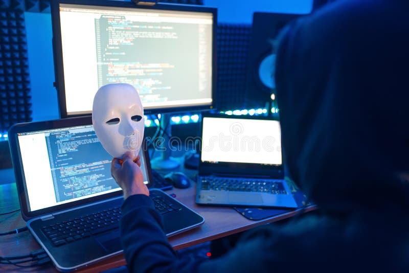 Ο χάκερ στην κουκούλα κρατά μάσκα στο χέρι, εγκληματικός τρόπος ζωής στοκ εικόνες