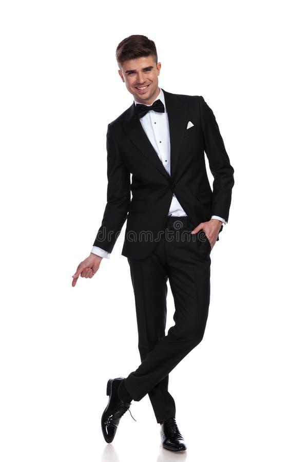 Ο χαλαρωμένος χαρούμενος επιχειρηματίας στέκεται cross-legged και δείχνει την πλευρά στοκ εικόνες με δικαίωμα ελεύθερης χρήσης