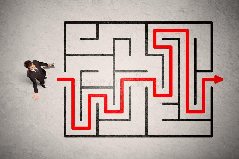 Ο χαμένος επιχειρηματίας βρήκε τον τρόπο στο λαβύρινθο με το κόκκινο βέλος στοκ φωτογραφίες με δικαίωμα ελεύθερης χρήσης