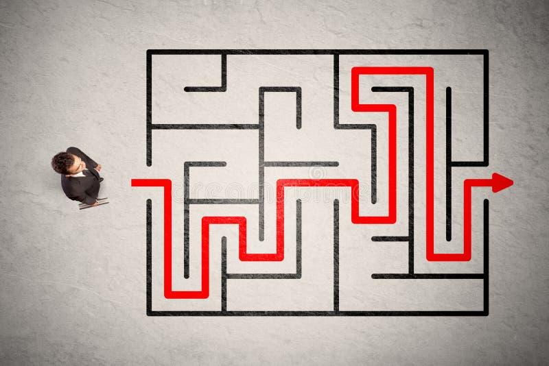 Ο χαμένος επιχειρηματίας βρήκε τον τρόπο στο λαβύρινθο με το κόκκινο βέλος στοκ φωτογραφία με δικαίωμα ελεύθερης χρήσης