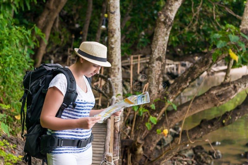 Ο χαμένος τουρίστας με έναν χάρτη και ένα σακίδιο πλάτης κοιτάζει στοκ εικόνα με δικαίωμα ελεύθερης χρήσης