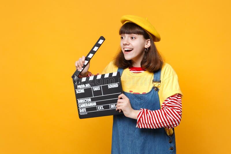 Ο χαμογελώντας έφηβος κοριτσιών γαλλικό beret που κοιτάζει κατά μέρος, που κρατά την κλασική μαύρη παραγωγή ταινιών clapperboard  στοκ φωτογραφίες με δικαίωμα ελεύθερης χρήσης