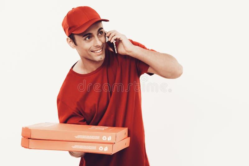 Ο χαμογελώντας αγγελιαφόρος πορτοκαλή σε ομοιόμορφο μιλά στο τηλέφωνο στοκ φωτογραφία με δικαίωμα ελεύθερης χρήσης