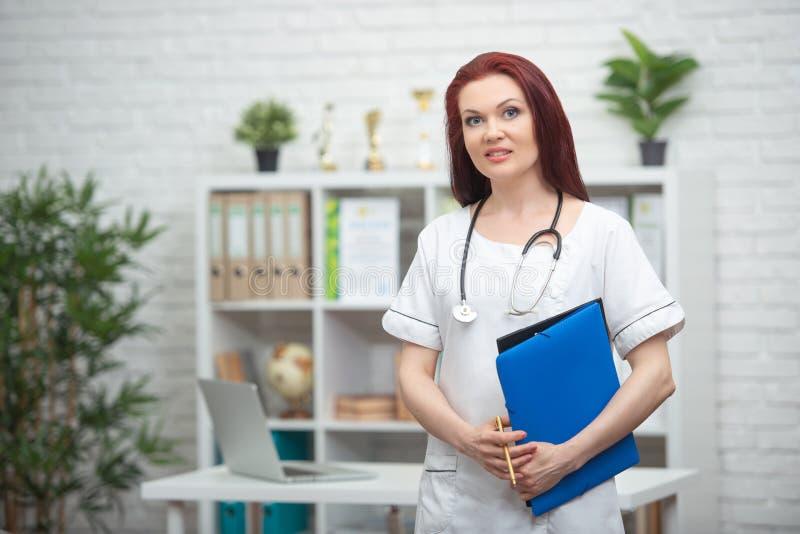 Ο χαμογελώντας θηλυκός γιατρός σε ομοιόμορφο με ένα στηθοσκόπιο και έναν μπλε φάκελλο στα χέρια της στέκεται στο ιατρικό γραφείο  στοκ φωτογραφία με δικαίωμα ελεύθερης χρήσης