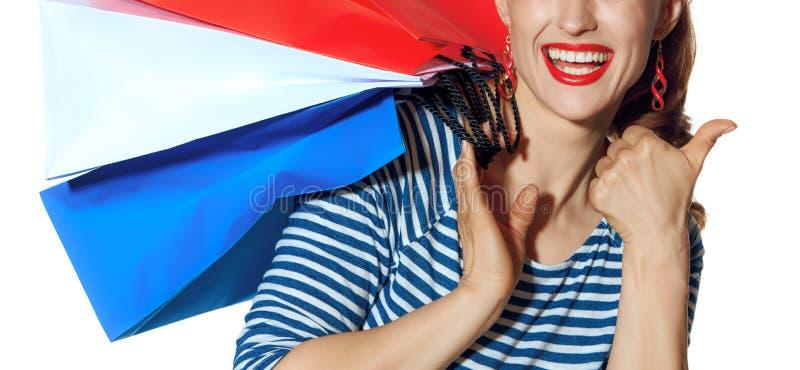 Ο χαμογελώντας μόδα-έμπορος στην άσπρη παρουσίαση υποβάθρου φυλλομετρεί επάνω στοκ φωτογραφία με δικαίωμα ελεύθερης χρήσης