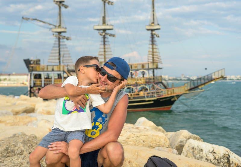 Ο χαμογελώντας νέος πατέρας φιλά το γιο κοντά στη θάλασσα στο ηλιοβασίλεμα ευτυχές καλοκαίρι ημερώ& Έννοια της φιλικής οικογένεια στοκ φωτογραφίες με δικαίωμα ελεύθερης χρήσης