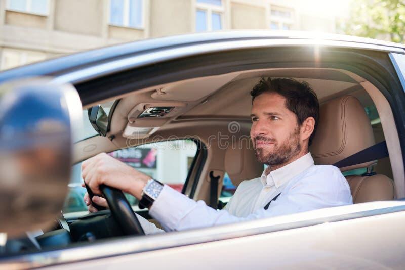 Ο χαμογελώντας νεαρός άνδρας που οδηγεί το αυτοκίνητό του κατά τη διάρκεια του πρωινού του ανταλάσσει στοκ φωτογραφία