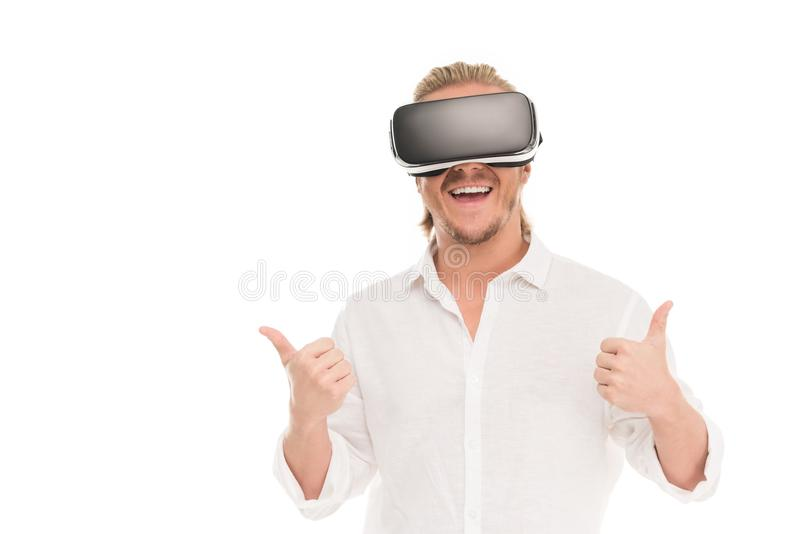 ο χαμογελώντας νεαρός άνδρας στην παρουσίαση κασκών εικονικής πραγματικότητας φυλλομετρεί επάνω στοκ εικόνα