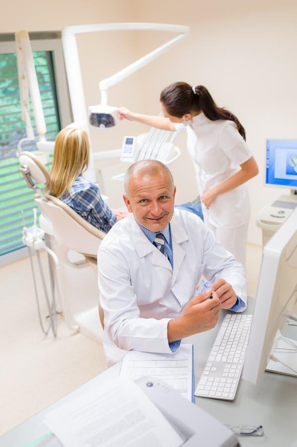 Ο χαμογελώντας οδοντικός χειρούργος εμφανίζει μοντέλο των δοντιών στοκ εικόνες