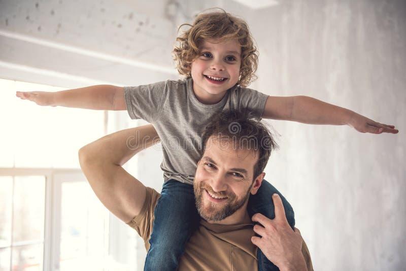 Ο χαμογελώντας πατέρας ανατρέφει προσεκτικά το γιο στους ώμους στοκ εικόνες