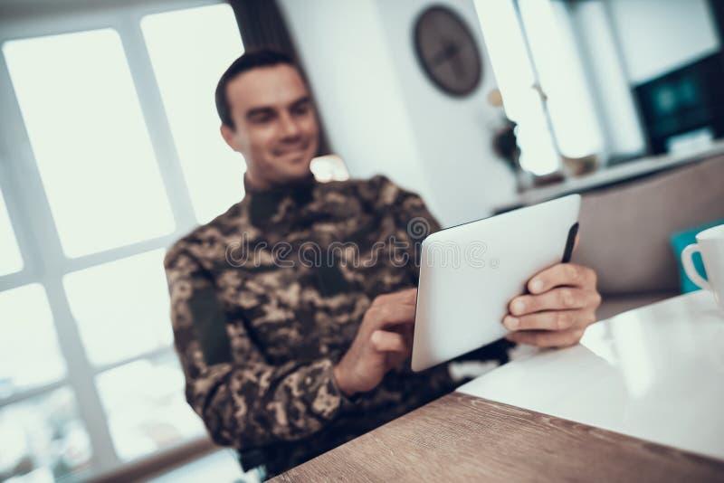 Ο χαμογελώντας στρατιωτικός χρησιμοποιεί την ταμπλέτα στο καθιστικό στοκ εικόνες
