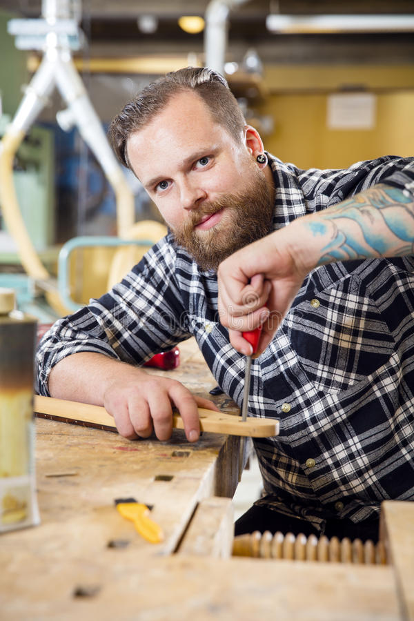 Ο χαμογελώντας βιοτέχνης αρχειοθετεί τον ξύλινο λαιμό κιθάρων στο εργαστήριο στοκ φωτογραφίες με δικαίωμα ελεύθερης χρήσης