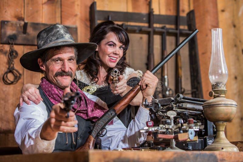 Ο χαμογελώντας σερίφης δείχνει το πυροβόλο όπλο με τη γυναίκα στοκ εικόνες