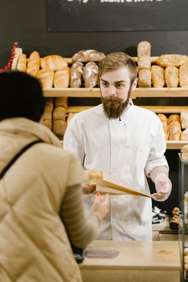 Ο χαρισματικός αρτοποιός με μια γενειάδα και mustache δίνει μια τσάντα εγγράφου του ψωμιού στον πελάτη στο αρτοποιείο στοκ φωτογραφία με δικαίωμα ελεύθερης χρήσης