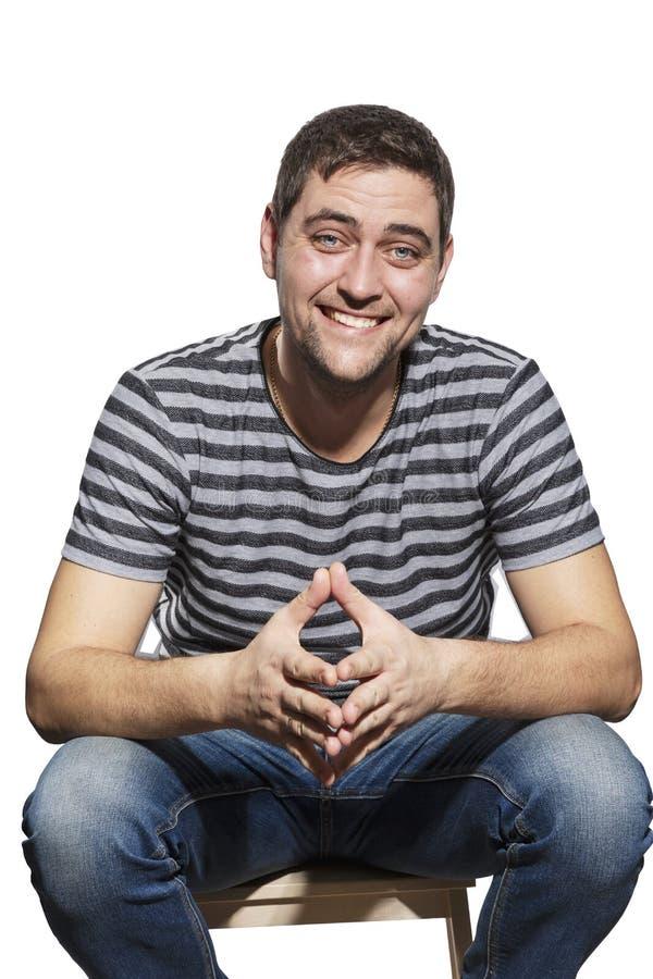 Ο χαριτωμένος γελώντας νεαρός άνδρας κάθεται σε μια καρέκλα στοκ φωτογραφία με δικαίωμα ελεύθερης χρήσης