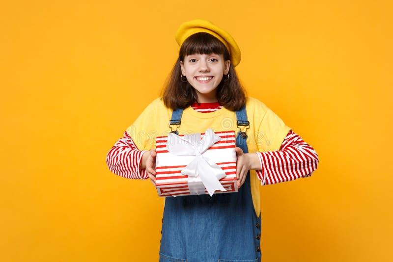 Ο χαρούμενος έφηβος κοριτσιών γαλλικό beret, κόκκινο ριγωτό παρόν κιβώτιο εκμετάλλευσης τζιν sundress με την κορδέλλα δώρων απομό στοκ φωτογραφίες με δικαίωμα ελεύθερης χρήσης