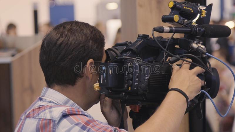 Ο χειριστής αφαιρεί μια έκθεση σχετικά με την επαγγελματική κάμερα Ο χειριστής αφαιρεί τη κάμερα στοκ εικόνα με δικαίωμα ελεύθερης χρήσης