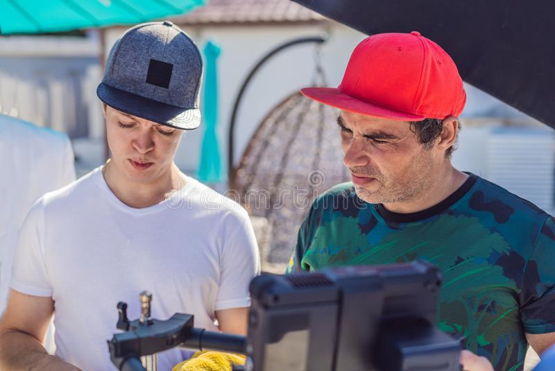 Ο χειριστής καμερών, ο διευθυντής της φωτογραφίας και ο διευθυντής συζητούν τη διαδικασία ενός εμπορικού τηλεοπτικού βλαστού στοκ φωτογραφίες με δικαίωμα ελεύθερης χρήσης