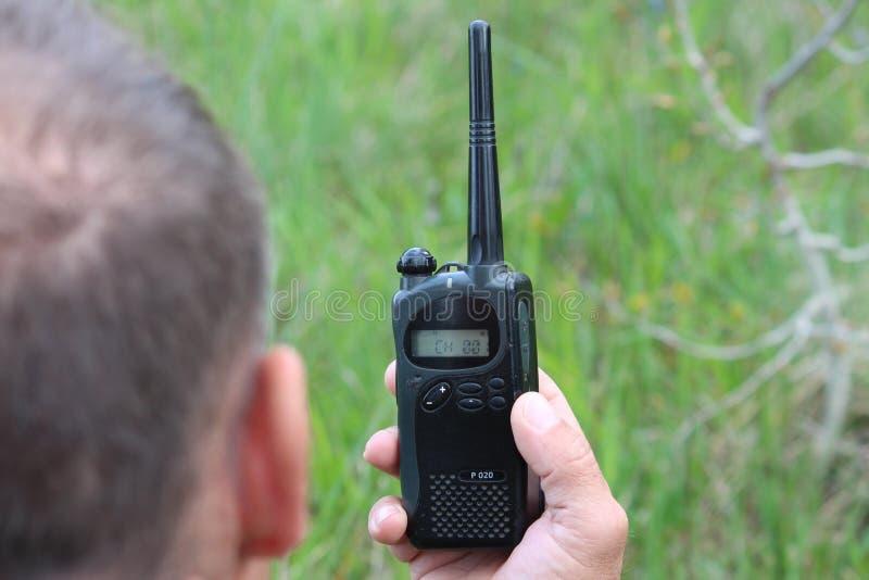 Ο χειριστής στον εργασιακό χώρο διαθέτει τους εργαζομένους με ένα walkie-TA στοκ εικόνα
