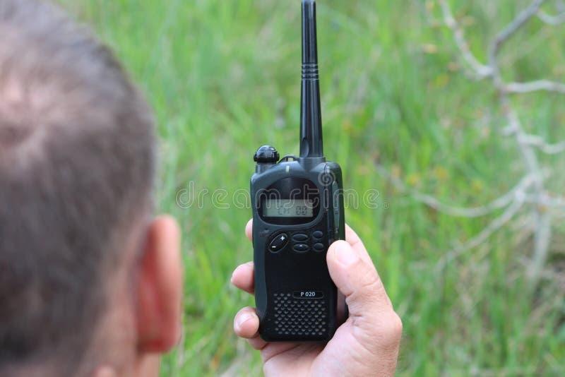 Ο χειριστής στον εργασιακό χώρο διαθέτει τους εργαζομένους με ένα walkie-TA στοκ φωτογραφία