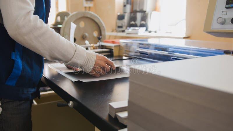 Ο χειριστής τυπωμένων υλών τραβά το τυπωμένο φύλλο του εγγράφου στοκ εικόνες με δικαίωμα ελεύθερης χρήσης