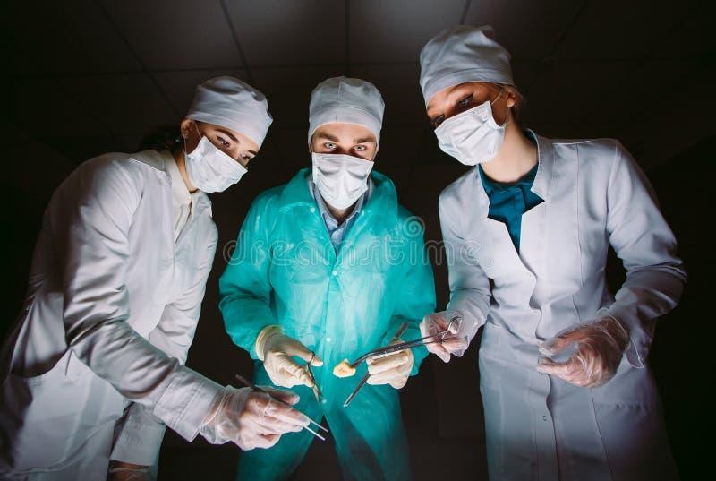 Ο χειρούργος κάνει μια λειτουργία σε ένα σκοτεινό δωμάτιο στοκ εικόνα