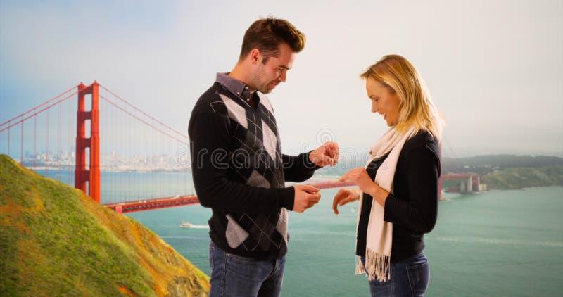 Ο χιλιετής φίλος προτείνει στη φίλη μπροστά από τη χρυσή γέφυρα πυλών στοκ εικόνα