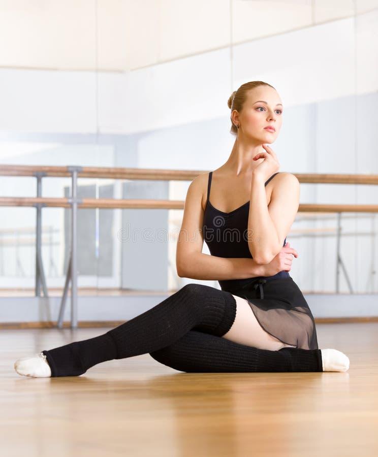 Ο χορευτής μπαλέτου επιλύει τη συνεδρίαση στο πάτωμα στοκ εικόνα