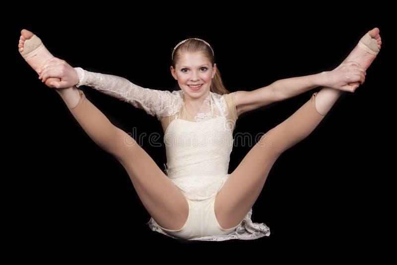 Ο χορός νέων κοριτσιών κάθεται τα πόδια λαβής επάνω στοκ φωτογραφίες